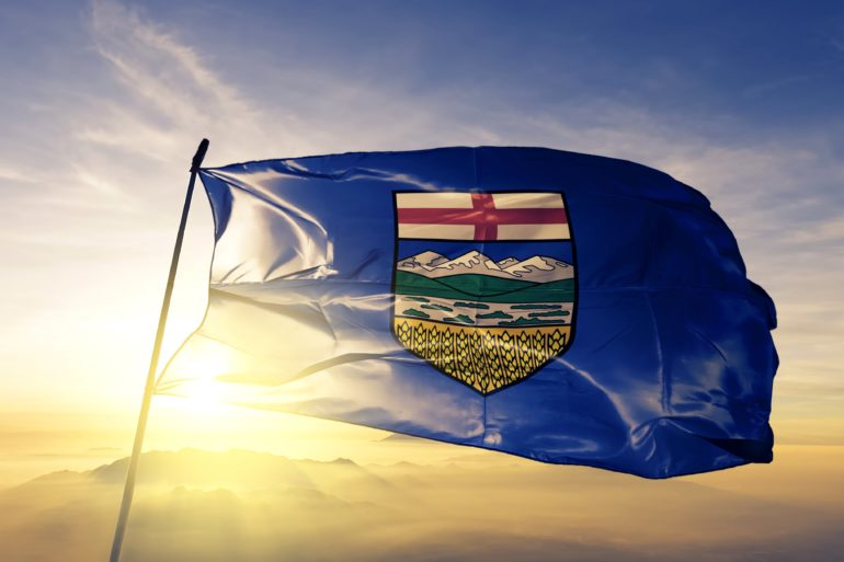 Alberta flag in front of the sun setting over the mountains.